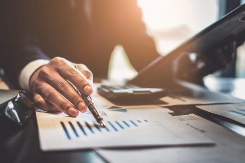 Small Business Grants, Close up Businessman consultant holding pen and pointing at financial on wooden desk in coffee shop. freelance, tax, accounting, statistics and analytic research concept.