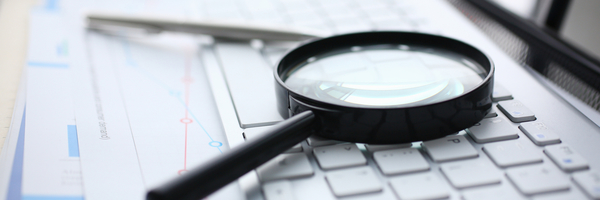external audit, Magnifying glass lies on white keyboard